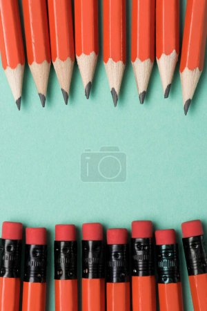 top view of graphite pencils and erasers on pencils placed in rows on green