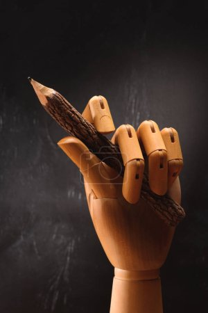 close up of wooden hand holding pencil in front of empty chalkboard in school