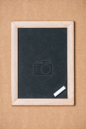 top view of empty blackboard and piece of chalk on brown background