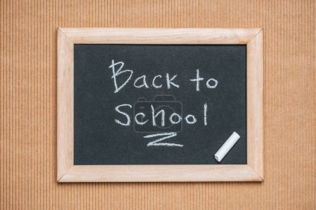 Photo for Top view of blackboard with back to school inscription and piece of chalk on brown background - Royalty Free Image