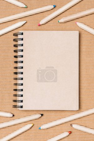 flat lay with arrangement of empty notebook and colorful pencils on brown backdrop