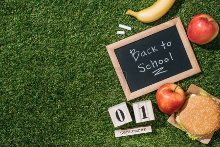 flat lay with blackboard with back to school lettering, calendar, banana, apples and burger on green grass
