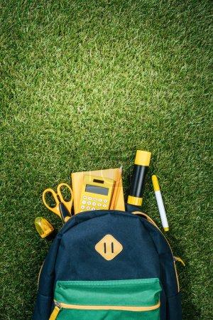 lay plat avec sac à dos arrangé et fournitures de bureau sur l'herbe verte