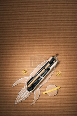 top view of handmade cardboard rocket with stationery and planet on brown background