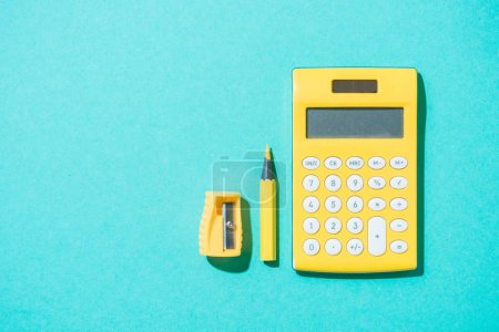 top view of arrangement of calculator, pencil and pencil sharpener on blue backdrop