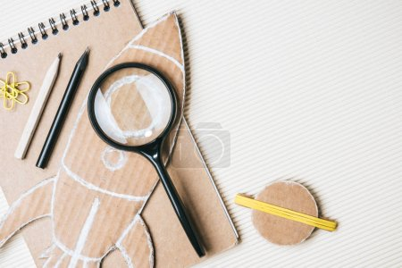 top view of handmade cardboard rocket and planet, magnifying glass, notebook and pencils on white background