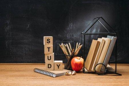 Photo pour Vue rapprochée de l'inscription de l'étude en blocs de bois, cahier, pomme fraîche et livres sur la surface avec tableau noir vide derrière - image libre de droit