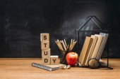 close up view of study inscription made of wooden blocks, notebook, fresh apple and books on surface with empty blackboard behind