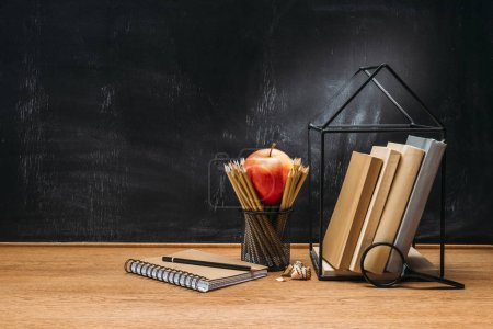 close up view of fresh apple, magnifying glass, notebook and books on wooden surface with empty blackboard behind