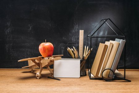 close up view of apple on wooden toy plane, notebook, books and pencils on tabletop with empty blackboard behind