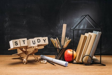 close up view of wooden toy plane, study inscription made of blocks, books and pencils on tabletop with empty blackboard behind