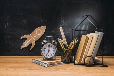 close up view of cardboard rocket on blackboard, pencils, clock, notebook and books on wooden tabletop