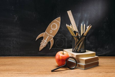 close up view of cardboard rocket on blackboard, apple, magnifying glass and books on wooden tabletop