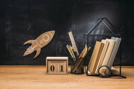 close up view of cardboard rocket on blackboard, calendar, magnifying glass and books on wooden tabletop
