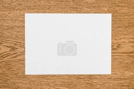 elevated view of empty white paper on wooden table
