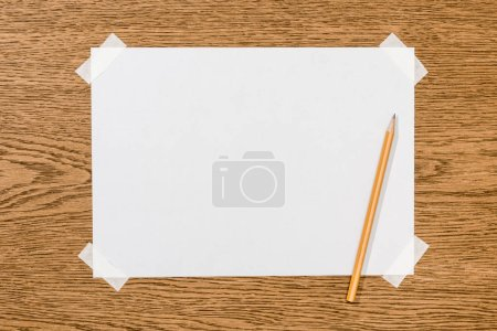 top view of blank white paper and graphite pencil on wooden table