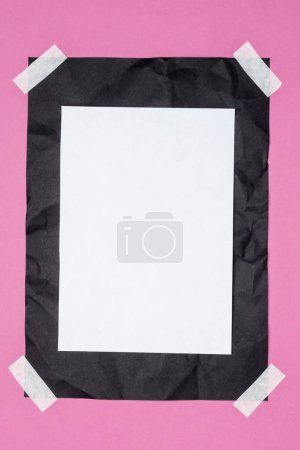 top view of empty white paper on black crumpled paper on pink