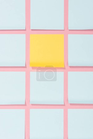 elevated view of empty blue and yellow stick it notes on pink