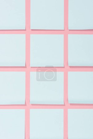 top view of set of blank blue stick it notes on pink