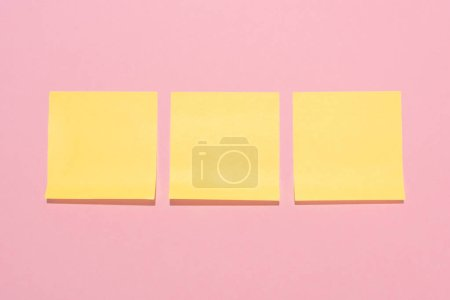 top view of blank yellow stick it notes placed in row on pink