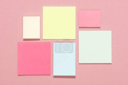 top view of empty colorful stick it notes on pink