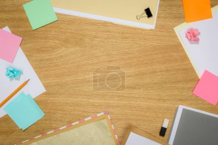 top view of table with blank papers and stick it notes with stationery supplies on table