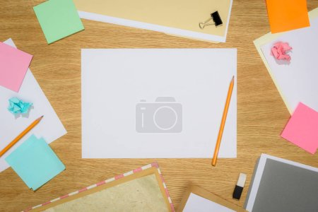 elevated view of empty papers with pencils and stationery supplies on wooden table