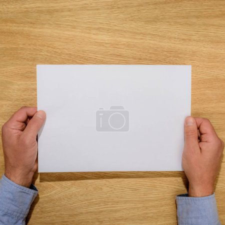 Photo for Cropped image of man holding empty white paper over wooden table - Royalty Free Image