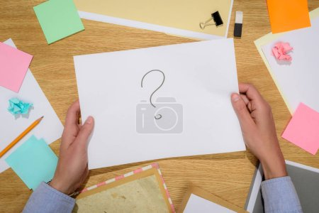 Foto de Recortar imagen de la mujer sujeta papel con signo de interrogación sobre tabla con palo señala y suministros de papelería - Imagen libre de derechos