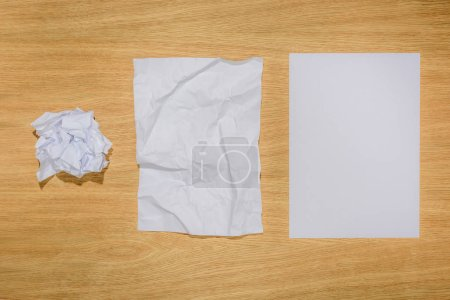 top view of crumpled papers and blank white paper on wooden table