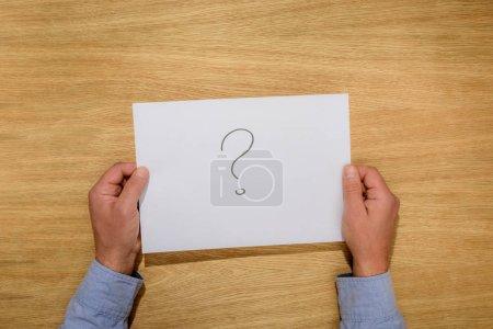 Foto de Recortar imagen de hombre que sostiene el papel con el signo de interrogación sobre mesa de madera - Imagen libre de derechos