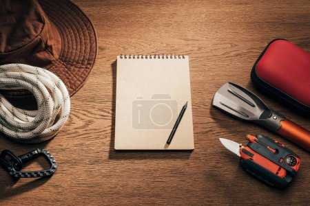 top view of blank notepad with pencil and trekking and hiking items on wooden table