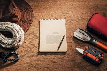 Photo pour Vue du dessus du bloc-notes vierge avec crayon et articles de trekking et de randonnée sur table en bois - image libre de droit