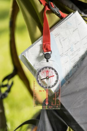 close-up view of compass hanging on backpack and map
