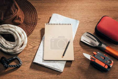 top view of blank notebook with pencil, map and travel items on wooden table