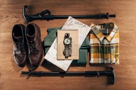 flat lay with trekking sticks, compass, map and clothes with footwear on wooden table