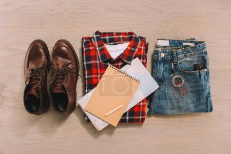 top view of notebook, map clothes and shoes on wooden surface