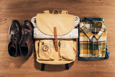 Photo for Top view of backpack with compass, map and clothes on wooden table - Royalty Free Image
