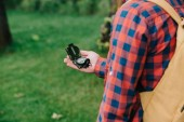 cropped shot of young man in checkered shirt holding compass in forest