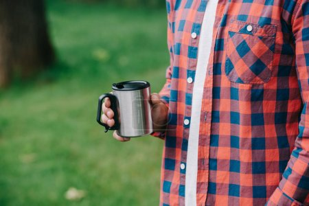 cropped shot of young man in checkered shirt holding mug outdoors
