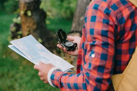 cropped shot of young male traveler holding compass and map in forest