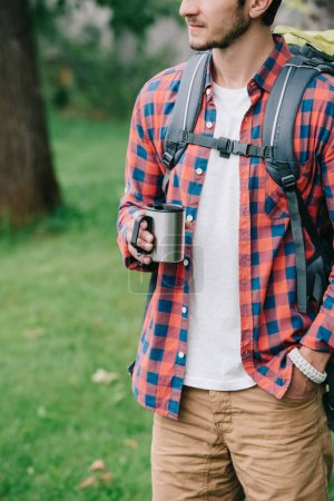 cropped shot of young man with backpack holding mug