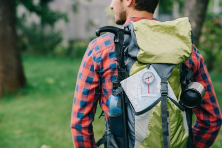 Photo pour Recadrée tir de voyageur de jeune homme avec sac à dos, boussole et carte - image libre de droit