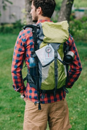 back view of young man traveler with backpack, compass and map