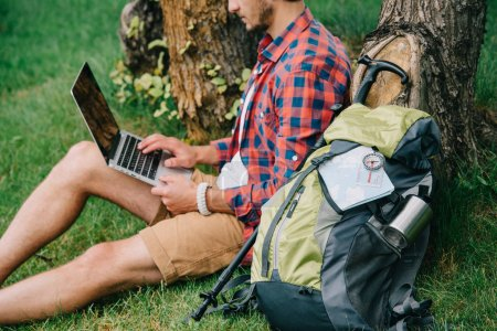 cropped shot of young man traveler using laptop with blank screen while sitting on grass
