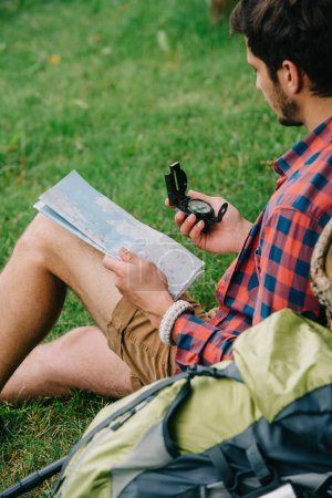 cropped shot of man holding map and compass while sitting on grass