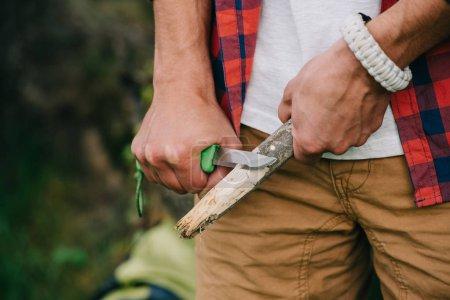 cropped shot of man sharpening log with knife
