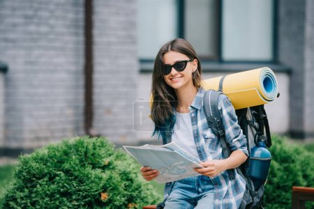 Photo for Happy young woman with backpack holding map and smiling at camera - Royalty Free Image