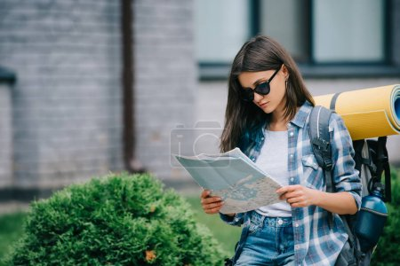 beautiful young female backpacker in sunglasses holding map