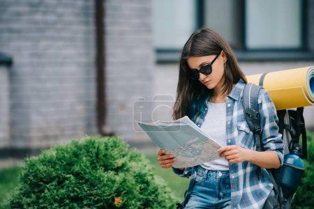 Photo pour Belle jeune femme routard en lunettes de soleil tenant carte - image libre de droit